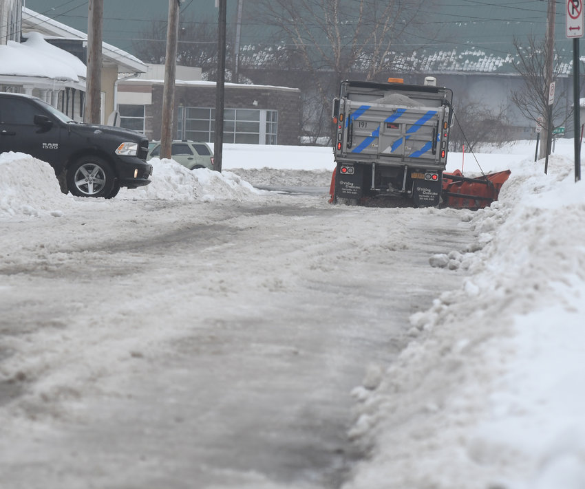 MONDAY CLEANUP CONTINUES — A city plow moves along Lawrence Street where there is such a substantial layer of ice that the street can't be cleaned on Monday, Feb. 10.