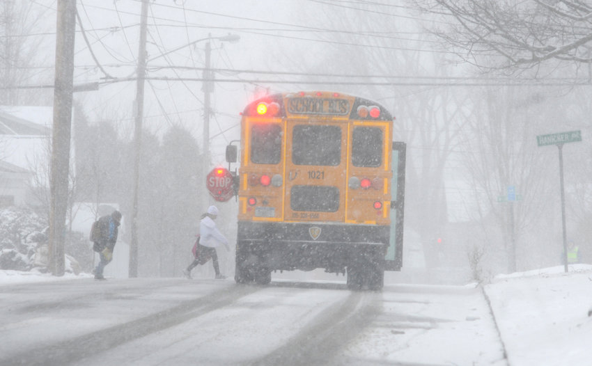 CAMERAS PROPOSED — A school bus stops to pick up students in Rome in this file photo. School buses would be outfitted with automatic cameras recording the license plates of vehicles that pass stopped school buses under a proposal headed to Oneida County lawmakers.