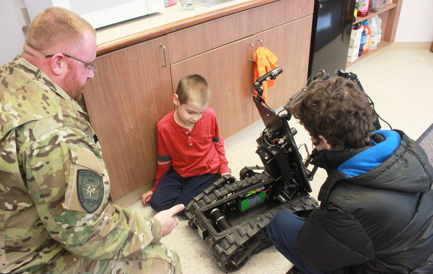 INNER WORKINGS — Sergeant Chad Chapman of the Madison County Sheriff Department's Special Operations Unit shows Travis Rounds, 7, center, and Gabriel Stone, 12, the inside of Chappie, the department's mobile reconnaissance robot.