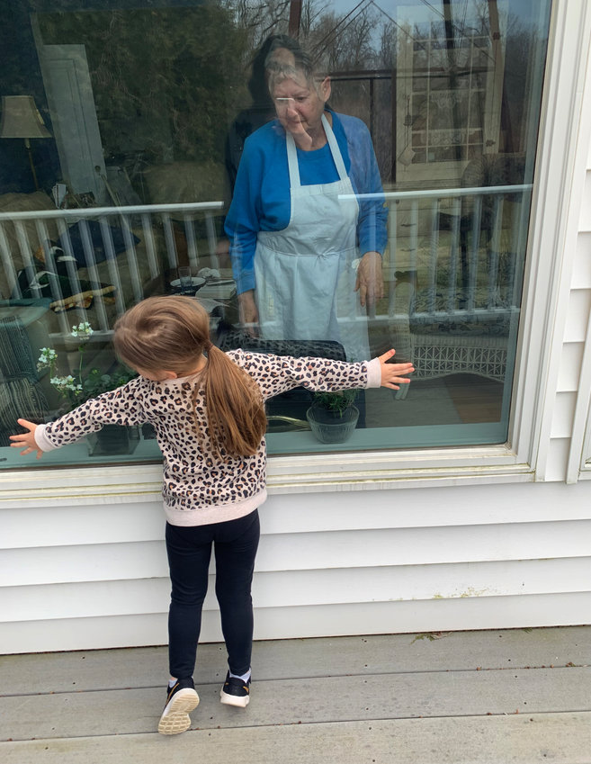 HUG THROUGH THE GLASS — Natalie Genovese, 4, may not be able to physically give grandma Virginia Consiglio a big squeeze but that doesn't stop the youngster from sharing her love with a hug through the window at Consiglio's 301 Mohawk St. home last week. While social distancing may keep many physically apart, Genovese, the daughter of James and Nicole Genovese, shows how to overcome the separation.