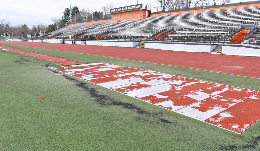 TURF AND TRACK ISSUES — A jump pit area at Rome Free Academy Stadium is covered for the off-season, while some dark granular materials from the nearby turf can be seen next to it. The worn-out turf and track are to be replaced later this year.
