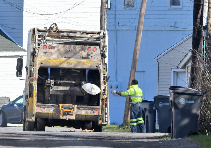 TOSSED AWAY —A crew from Controlled Waste Systems, Inc., collects garbage on Massock Avenue in south Rome this morning. Residents issues with trash collection was discussed during Wednesday night's Common Council meeting.
