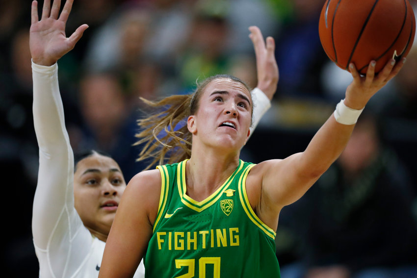 DRIVING TO THE BASKET — In this Feb. 1 file photo, Oregon guard Sabrina Ionescu, front, drives to the basket past Colorado guard Lesila Finau during the first half of a college basketball game in Boulder, Colo. Ionescu and Iowa wrestler Spencer Lee shared the Sullivan Award on Wednesday night as the country's top amateur athlete.