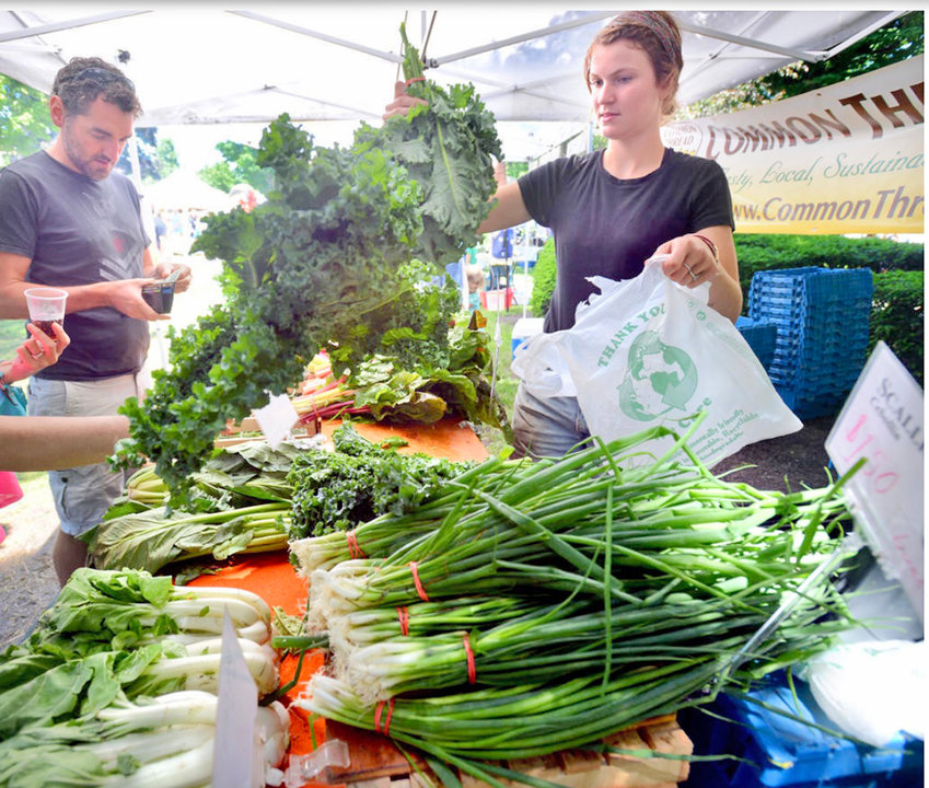 """SELECT AND GO — Stephanie Joyce of Common Thread Farm waits on Dave Griffin at the Clinton Farmer's Market in 2014. In 2020 customers will be asked to select what they'd like and exit the green. A policy change due to the """"new normal"""" circumstances brought on by the coronavirus/COVID-19 pandemic."""