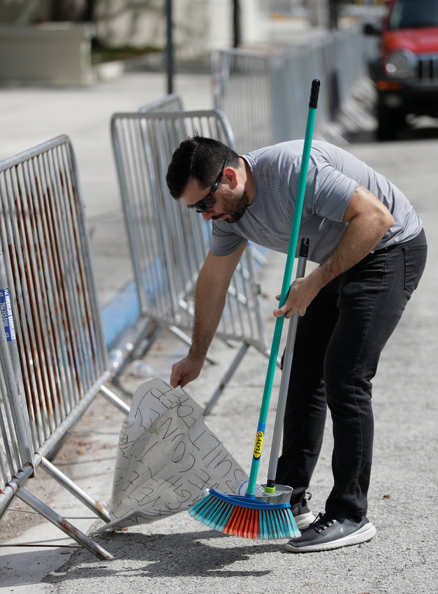 BIG SWEEP — Volunteer Carlos Suaza pickups up a discarded sign and trash from in front of the City of Miami Police Department Monday  where protesters demonstrated the night before in downtown Miami, in reaction to George Floyd's death while in police custody.