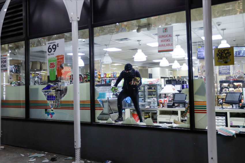 WINDOW ESCAPE — A person carries merchandise from a 7-Eleven store Monday in New York. Larger stores, including Macy's flagship downtown building, were ransacked.