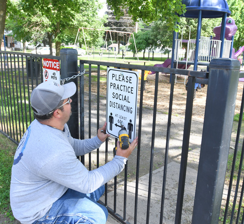 READY FOR PLAY — City of Rome Parks worker Lenny Costello places a sign at the gate at the Franklyn's Field playground this morning, urging users to practice social distancing, as the facilities were opened. City pools will not open this year, Mayor Jacqueline M. Izzo confirmed, and other recreation facilities may open later as part of phase four of the state's economic reopening.