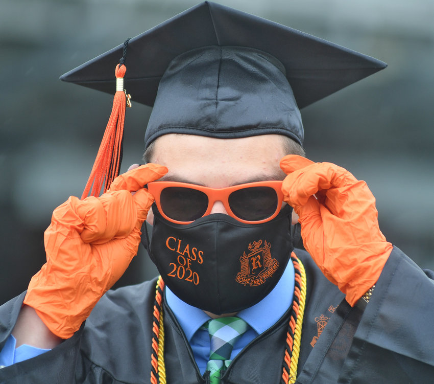 BRIGHT FUTURE —Brett Faroni, a member of the RFA Class of 2020, fixes his sunglasses as he and a group of classmates begin a day of mini-commencement ceremonies. With masks, gloves — and umbrellas —students received a ceremony that seemed unlikely just weeks ago.