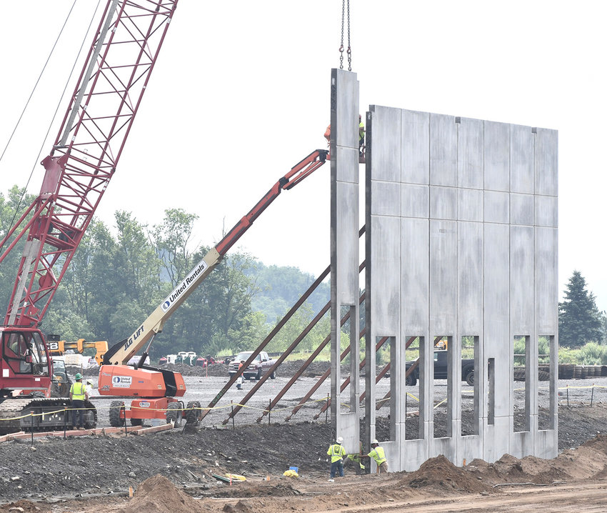 """GOING UP — A construction crew, using a massive crane as well as old fashioned """"elbow grease"""" put up the first panels of one of the walls of the future Orgill Distribution Center off of Route 825 across from the Wingate by Wyndham hotel. Tennessee-based Orgill is building an 800,000-square-foot distribution center to serve independent hardware and building supply stores in the Northeast. The company expects the facility to create some 225 new jobs."""