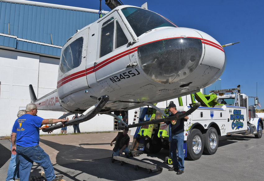 EASY DOES IT — Volunteers help lower the Vietnam-era helicopter from Missouri that was delivered to Griffiss Business and Technology Park's Mohawk Valley Community College Airframe and Powerplant Technology school Saturday.