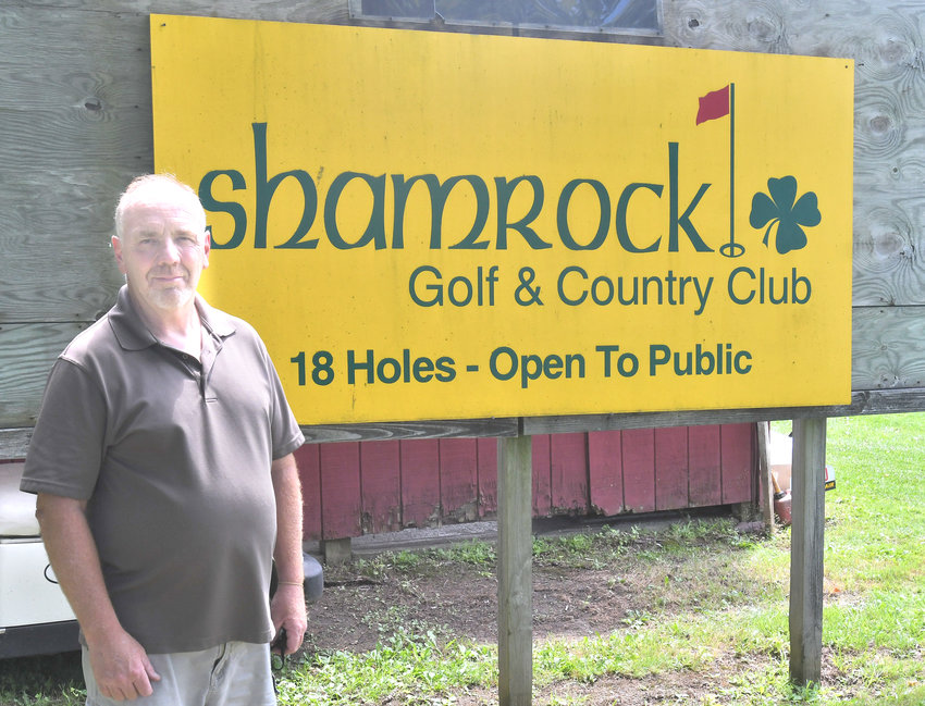 WELCOME TO SHAMROCK — Owner Matt Reed stands by a sign for Shamrock Golf and Country Club on Friday afternoon.
