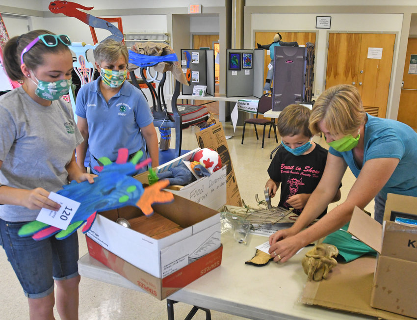 GETTING READY FOR THE SHOW —Ella Larry, 14, left, and Lynette Kay, 4-H Program Educator from Cornell Cooperative Extension of Oneida County, look on as Blaise Larry gets a little help from his mom, Cilla Larry, earlier this week at the Cooperative Extension offices in Whitestown. The Larrys, of Floyd, are among dozens of area 4-H members who will display a variety of projects at the Peterpaul Recreation Park, 5615 Rome-New London Road. The display will be open from 11 a.m. to 7 p.m. Friday, Aug. 14, through Monday, Aug. 17, and from 11 a.m. to 3 p.m. on Tuesday, Aug. 18.
