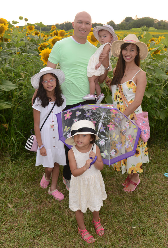 CAPTURING THE MOMENT —The Cruz family, who came all the way from Albany to enjoy the Wagner Farms sunflower fields, pose for a photo before taking their own selfies amid the late summer blooms. The family includes: Terence Cruz, holding Adeline Rose, 1; Evean Cruz, 9; mom Nelia Cruz; and Celyna Cruz, 3, with a cheerful umbrella.