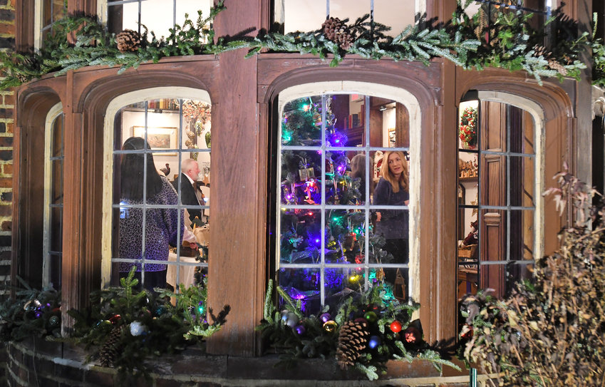 ON THE OUTSIDE LOOKING IN —Patrons enjoy the warmth and spirit of the Rome Art and Community Center's traditional Holiday House fundraiser. The festivities are gone this year, organizers say, as a result of the ongoing COVID-19 pandemic.