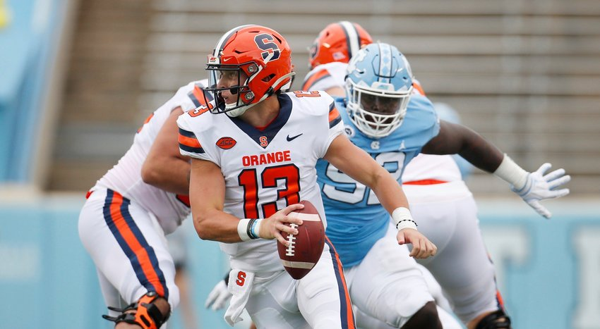 SCRAMBLING — Syracuse quarterback Tommy DeVito (13) scrambles to avoid North Carolina defender Jahlil Taylor (52) in first half of a college football game on Saturday in Chapel Hill, N.C.