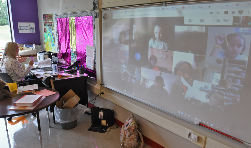 REMOTE LEARNING —Denti Elementary School first-grade teacher Candace Darois teaches her students remotely on Monday, during the first day of the 2020-21 academic year. She is speaking to students on her computer screen, and the computer image also is projected onto the screen at right. More photos online at www.romesentinel.com.