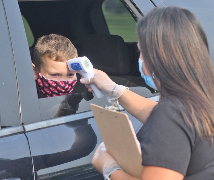 CHECK-IN — Logan Tyler, a third-grader at Westmoreland Upper Elementary School, gets his temperature taken by school nurse Sabrina Verdgeline on the first day of school on Tuesday, Sept. 8.
