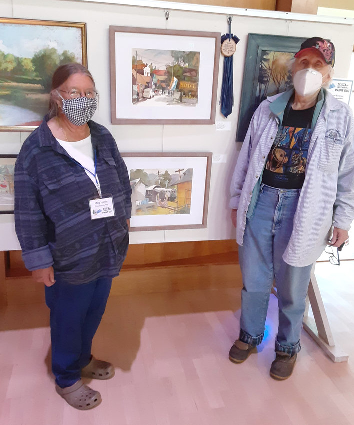 """BEST IN SHOW — Judge Martha Deming and Committee member Meg Harris stand beside the Best in Show selection, """"Old Forge"""" by Drayton Jones."""