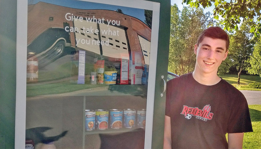 GIVE WHAT YOU CAN — 19-year-old Adam Fellows stands besides the pocket food pantry he built in the city of Sherrill, with food ready for anyone who needs it.