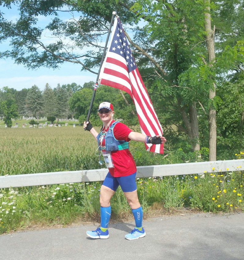 """FLAG LADY"" — Dr. Helen J. Knowles, walking in Clinton, plans to walk her virtual 26.2-mile Boston Marathon Jimmy Fund Walk starting at 8 a.m. Sunday, Oct. 4, beginning in her hometown and ending there, with a stop at the Sept. 11 Memorial in Utica along the way.  Knowles will represent the Red, White & Blue organization, which supports physical fitness and mental health awareness for veterans, and carry the American flag for the entire route."