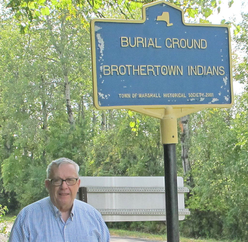 KIRKLAND HISTORIAN — Dick Williams, Kirkland Historian, stands by a sign indicating the Brothertown Indian cemetery off Brothertown Road in the Town of Marshall.