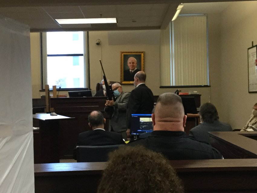 LOCK AND LOAD — Inv. David Cady demonstrates for the jury on Monday afternoon how to use the bolt-action rifle that law enforcers say Jason P. D'Avolio  used to murder his estranged wife Kerrilee D'Avolio.