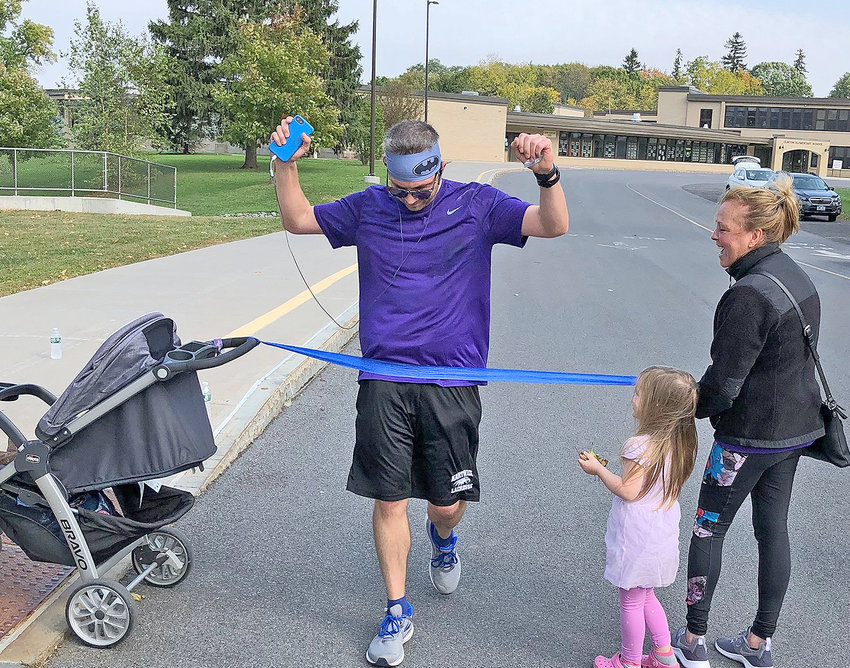 FINISH LINE — Mike Hoover, of Clinton, is welcomed at the finish line of his virtual marathon by his wife Nicole and daughter on the campus of Clinton Central School.  Hoover ran 26.2 miles donning his purple in support of the Alzheimer's Association.