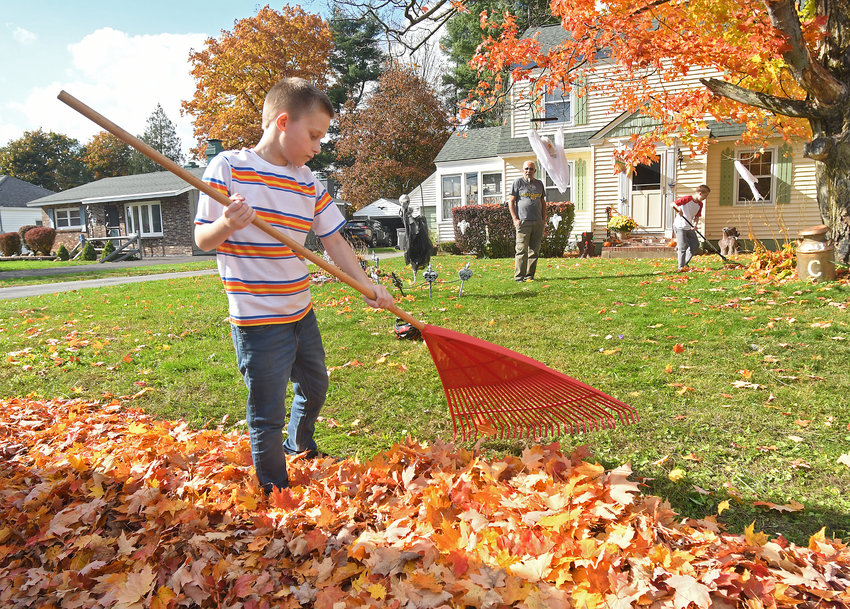 HELPING OUT —Dustin Pack, 10, and his brother in the background Shelby Pack, 12, rake up leaves at the home of their grandfather, Caesar Cruz, at 1513 Anken St. last week. Leaf collection in the city begins on Monday.