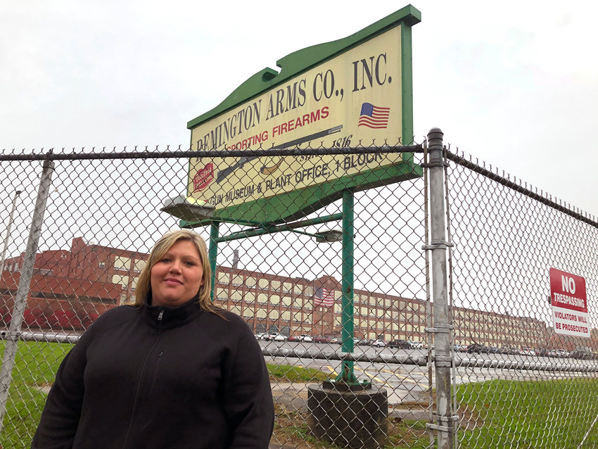 LET GO — Jacquie Sweeney stands outside the Remington firearms factory in Ilion recently. Sweeney and her husband were among almost 600 workers fired by the company last month, shortly after Remington Outdoor Co. sought bankruptcy protection for the second time in two years. Successful bidders for the idled plant in bankruptcy proceedings have said they plan to restart at least some production, though details remain scarce.