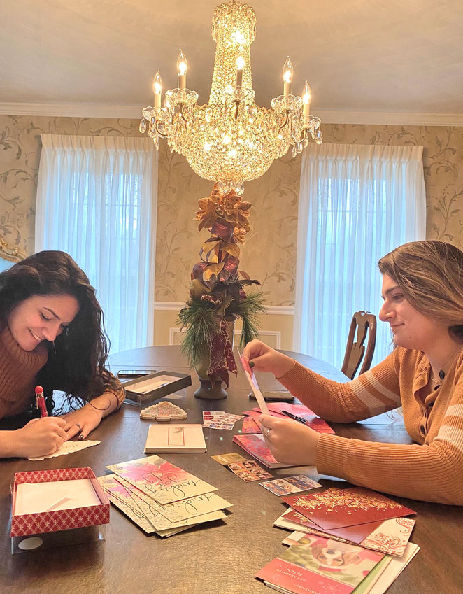 THINKING OF YOU —Alissa and Arica Tehan, of New Hartford, help out by writing messages of holiday cheer as part of the Cards Across America program. Alissa, an insurance professional, and Arica, a pharmacy student, are the granddaughters of Virginia Viscosi, one of the program organizers.