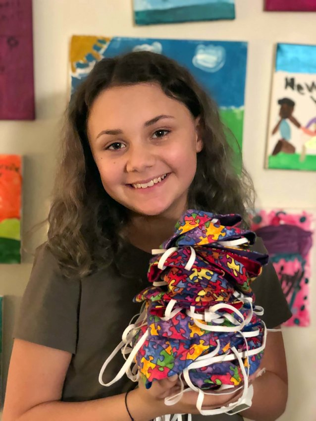 SPREADING JOY AND AWARENESS — CarolineHoltslander, 10, of Rome, smiles after completing a new batch of masks designed to promote autism awareness. Holtslander, who started her own business sewing masks at the start of the pandemic, has continued sewing masks to support The Kelberman Center, a local organization that provides services and supports to children and adults with autism.