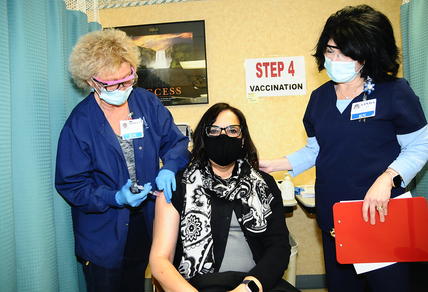 EQUAL PROTECTION — Rome NAACP President Jacqueline Nelson receives her first dose of Moderna vaccine on Friday at Rome Memorial Hospital.   Administering the vaccine are Rome Memorial Hospital nurses, Shirley Smith, RN, left, and Linda Lyon, RN.