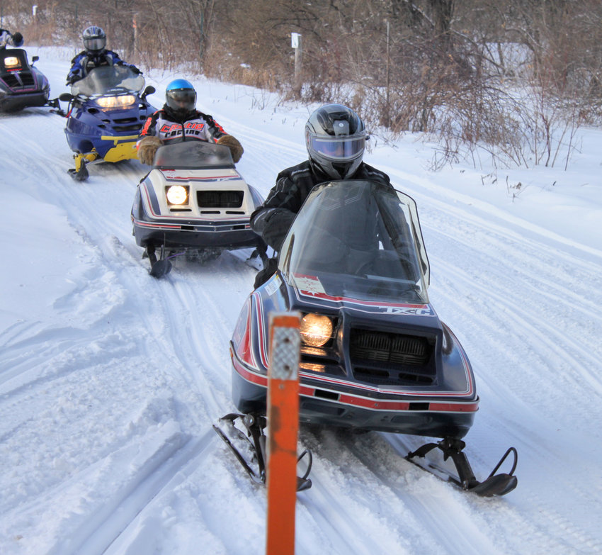 REMEMBERING A PIONEER —Riders on new and vintage sleds participate in a previous John Schoff Memorial Ride. This year's event will be held on Saturday, Jan. 23, starting at 10 a.m.Schoff was a pioneer of snowmobiling and the first Polaris dealer in the area.