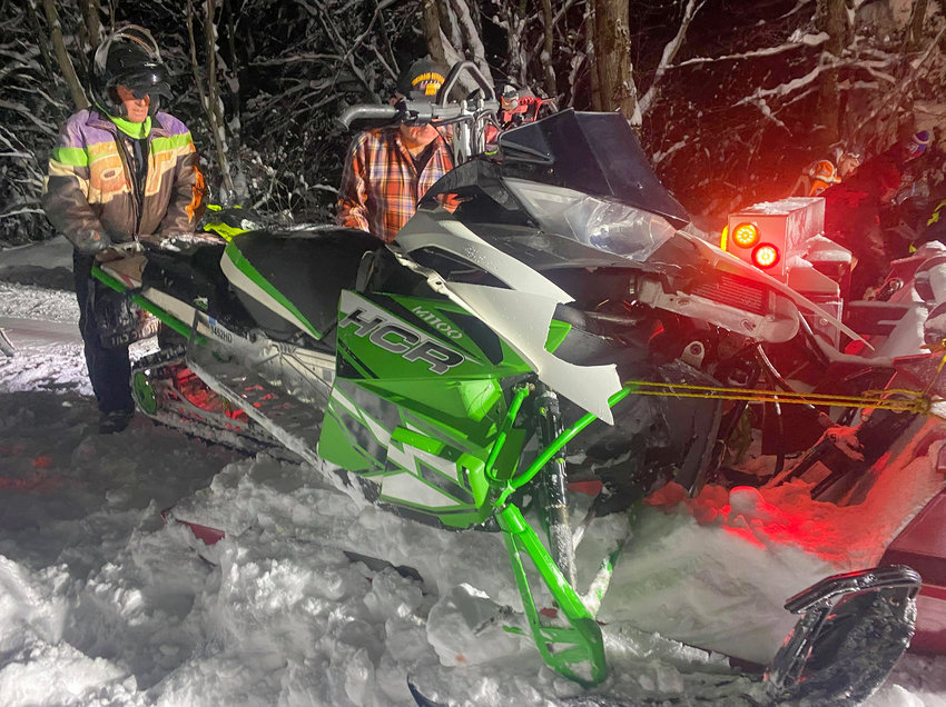 READY TO TOW — A snowmobiler watches as a sled is prepped for towing after a crash in Tug Hill on Monday. Operator Nicholas Finn, of Steuben, said he was lucky to walk away from the head-on collision in Lewis County. The operator of the other sled is believed to have been airlifted to a Syracuse hospital.