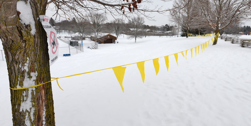 """SLIDE IN ANOTHER SPOT —Caution-pennant lines stretch across an area atop a hill at Lee Town Park where the town does not want people sledding because of safety concerns. On the tree at left is posted one of the signs that indicate """"Restricted No Sledding This Area."""""""