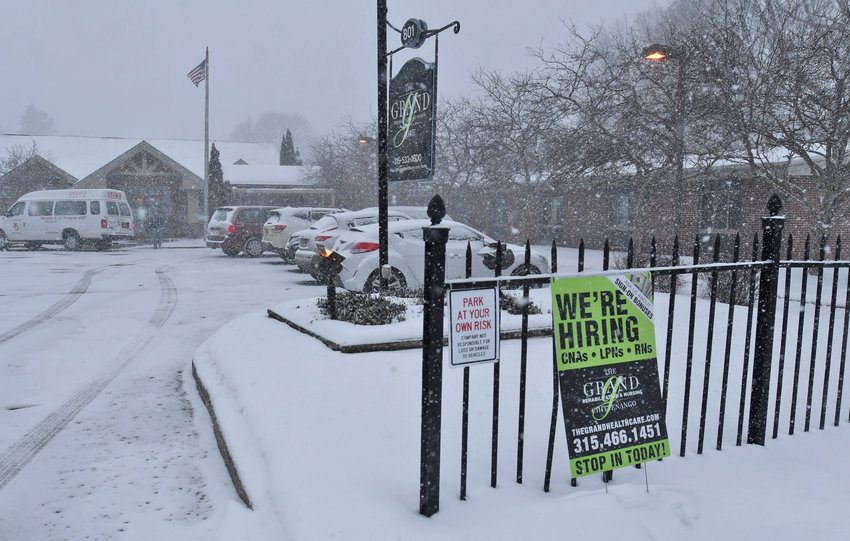 """HELP WANTED — A """"We're Hiring"""" sign is fixed to the fence outside The Grand Rehabilitation and Nursing Center, 801 N. James St., Tuesday.  Dozens of nursing homes, particularly those hard-hit in the first wave of the COVID-19 pandemic, report they are struggling to find workers."""