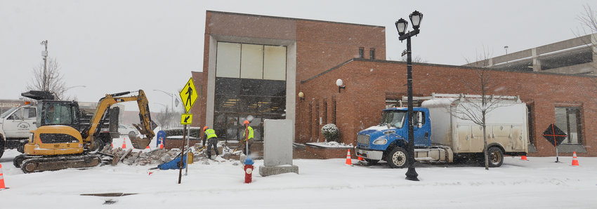 WORK IN PROGRESS — A crew from JS Septic and Sewer Service rips up the former fountain in front of the Berkshire Bank branch at the corner of North James and West Dominick streets on Tuesday. The fountain and clock were in disrepair, city officials said, adding that the bank decided to remove them rather than incur the expense of replacement. The branch, bank officials said, is expected to close at the end of April, with its operations moved to the branch at 1629 Black River Blvd.