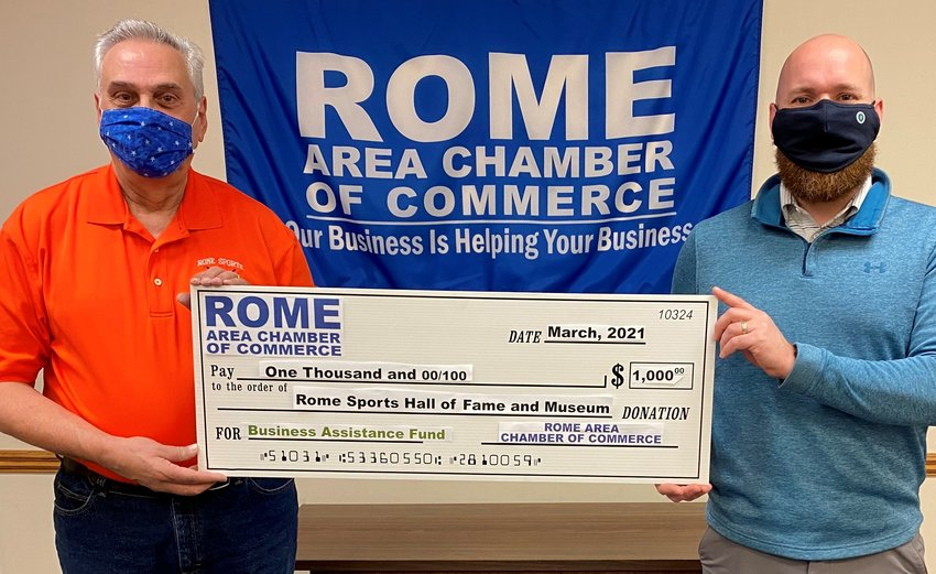 CONTINUING TO HONOR ROME'S SPORTS GREATS — David Sbaraglia, left,  executive director of theRome Sports Hall of Fame and Museum, 5790 Rome-New London Road, which is dedicated to honoring and preserving the great sports achievements of athletes of Rome, accepts a $1,000 check from the Rome Area Chamber of Commerce's Business Assistance Fund and Chamber Chairman Adam Hovak. The BAF was created to help local businesses weather the ongoing COVID-19 pandemic.