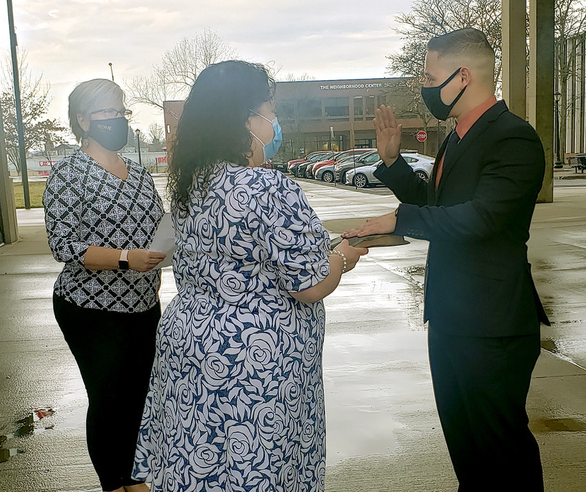 SWORN IN — Patrolman Wilfredo Huembes takes the oath of office for the Rome Police Department Friday morning. He was sworn in by City Clerk Jean Grande, left, with his mother holding the Bible. The small ceremony was held outside due to pandemic safety precautions.