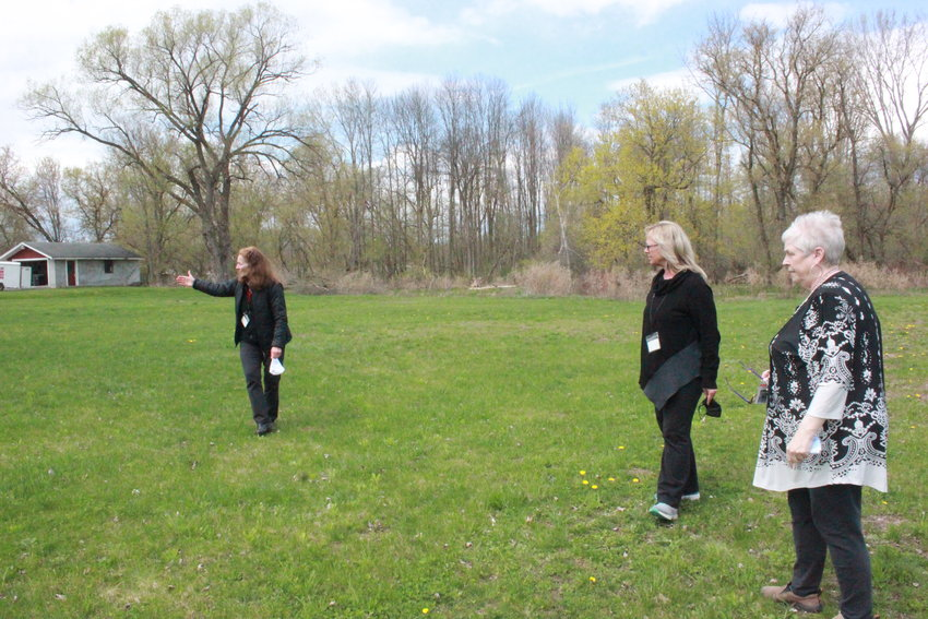 GARDEN IN THE MAKING — Mayor Helen Acker, right, Oneida Planning Director Cassie Rose, and Community Development Assistant Barbara Henderson walk through one of the fields in Oneida that will be used for the community garden program.