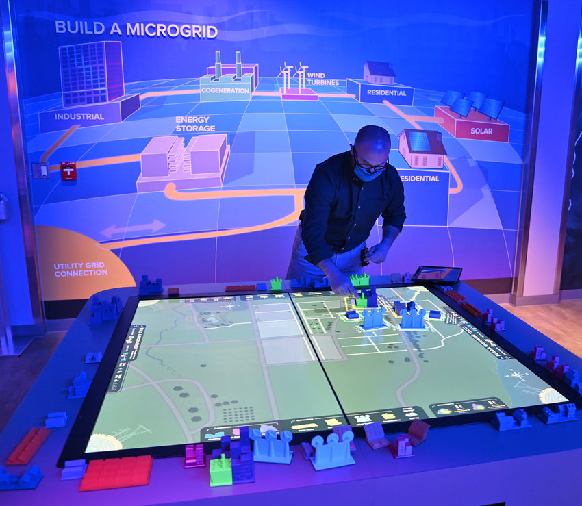 MICROGRID — Tour guide Mario Roefaro demonstrates how to build a microgrid in one of the many interactive exhibits at the John S. Dyson New York Energy Zone, which opens to the public on Monday. The admission-free New York Power Authority visitors center  is located at 35 Zoo Way in Utica. Additional photos online at www.romesentinel.com.