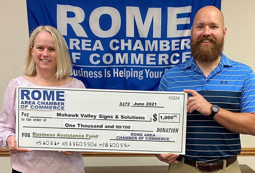 SIGN OF RECOVERY — Able to be mask free as statewide COVID-19 positivity rate declines and vaccination levels rise, Becky D'Aiuto, owner/president of Mohawk Valley Signs & Solutions, 5994 Judd Road in Whitestown, accepts a check for $1,000 from Adam Hovak, chairman of the Rome Area Chamber of Commerce, through the chamber's Business Assistance Fund.  Mohawk Valley Signs & Solutions is a full-service business specializing in producing commercial indoor and outdoor signs, including custom signs, vehicle wraps, and vinyl signs. For information, go online to https://mohawkvalleysigns.com/.