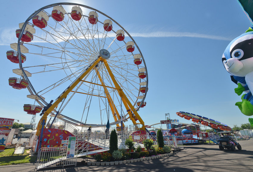 CROWDS OK TO RETURN —The Ferris wheel and other rides are set up on the midway at the New York State Fair in this file photo. Gov. Andrew M. Cuomo announced on Monday the State Fair can reopen at 100% capacity when it opens it gates on Aug. 20. The event, which will have some restrictions on the numbers of people allowed inside fair buildings, will run through Sept. 6.
