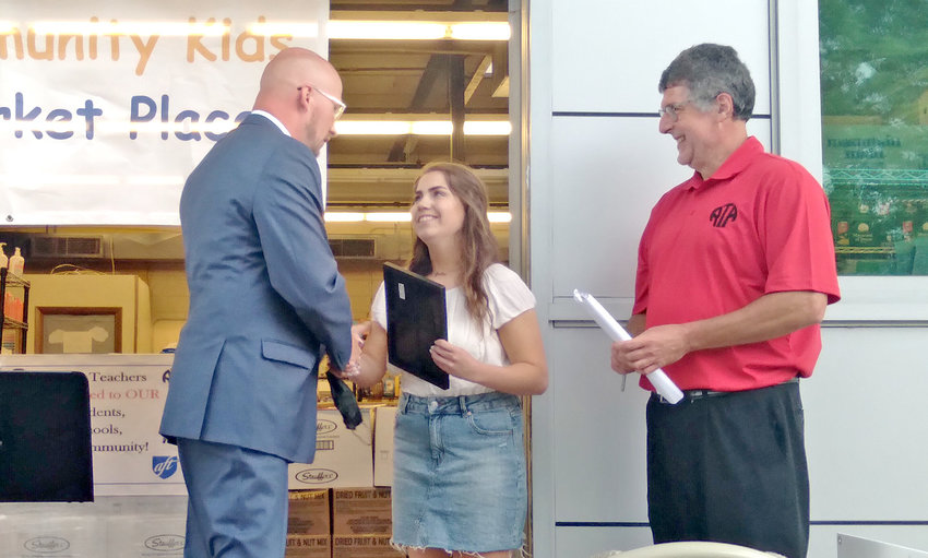 HAILED AS PIONEER — Rome Free Academy Senior Jordan Purrington accepts congratulations from Rome City School District Superintendent Peter C. Blake, left, while Rome Teachers Association President Robert Wood looks on. Purrington created the Coins for a Cause fundraiser to help students in need in the area.