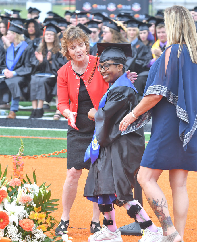 ON THE WAY — Kalani D. Willis-Alvarez, center, beams after getting up out of a wheelchair, flanked by guidance counselor Maureen Nash, left, and teacher assistant Noreen Nashton, and walked to get her diploma on Saturday during Rome Free Academy commencement ceremonies.