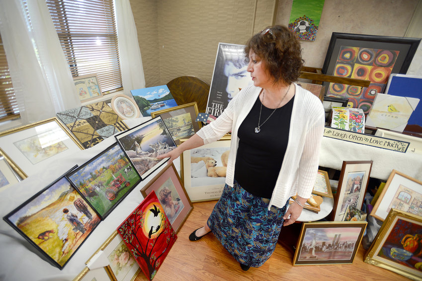 BRIGHTENING DAYS FOR ELDERLY — Theresa Girouard, executive director of the new Adopt-A-Wall Inc., project views some of the donations at its 107 W. Court St. location in Rome.  The project's goal is to supply wall coverings for nursing home residents to help brighten their surroundings. Drop-off locations are Enjem's in Utica, Big Apple Music in New Hartford, O'Baby's in New Hartford and Kinney's in Camden.