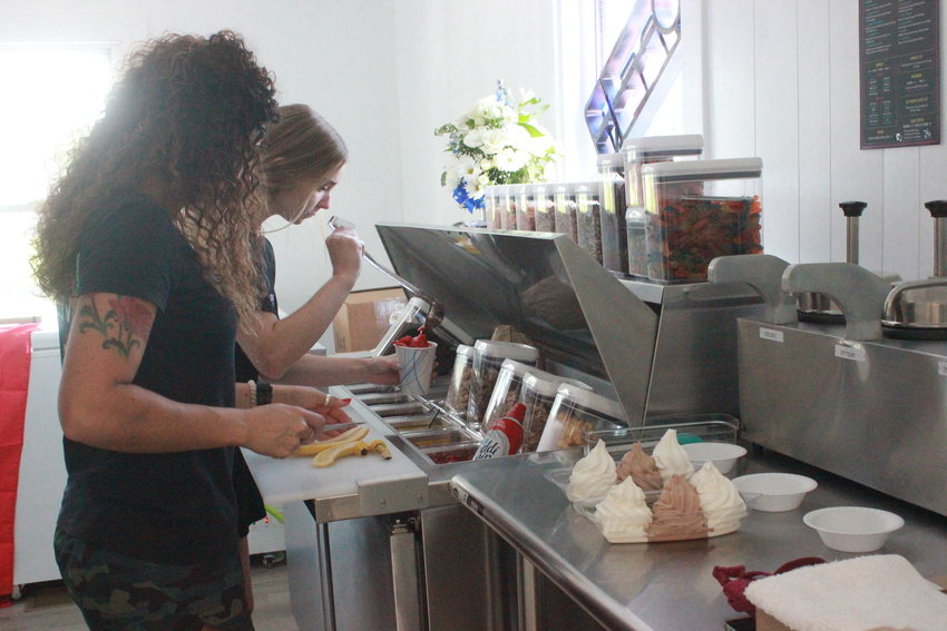SUNDAE SPLITS — Employees at the newly opened Coneheads in Oneida quickly craft treats for hungry customers on opening day.