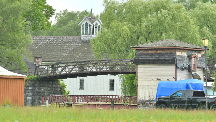 SEEKING TO RECOVER THE PAST — City and Rome Historical Society officials along with the new ownership of the former Erie Canal Village, with its buildings needing extensive repairs, are working to rehabilitate several structures and eye reopening the site as a historic location. Above, the village's bridge over the canal and Cheese Factory are shown.