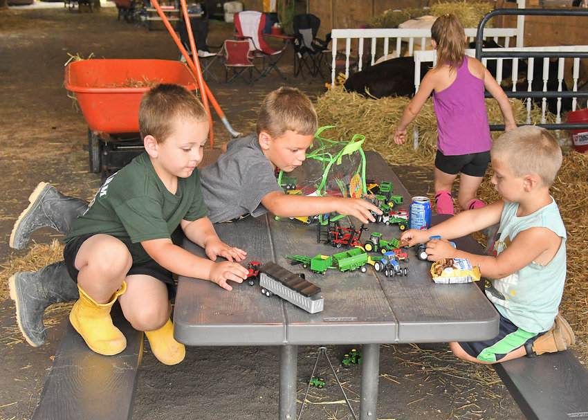 PLAYTIME IN BOONVILLE — Gordon Donahoe, 4, son of Casey Holbert of Clayville; Cole Frost, 4, and Evan Frost, 3, sons of Angela Frost of Pine Group Farm in Vernon play with their toy farm tractors in the livestock barn at the Boonville-Oneida County Fair on Tuesday afternoon. The fair opened Tuesday and runs through Sunday.