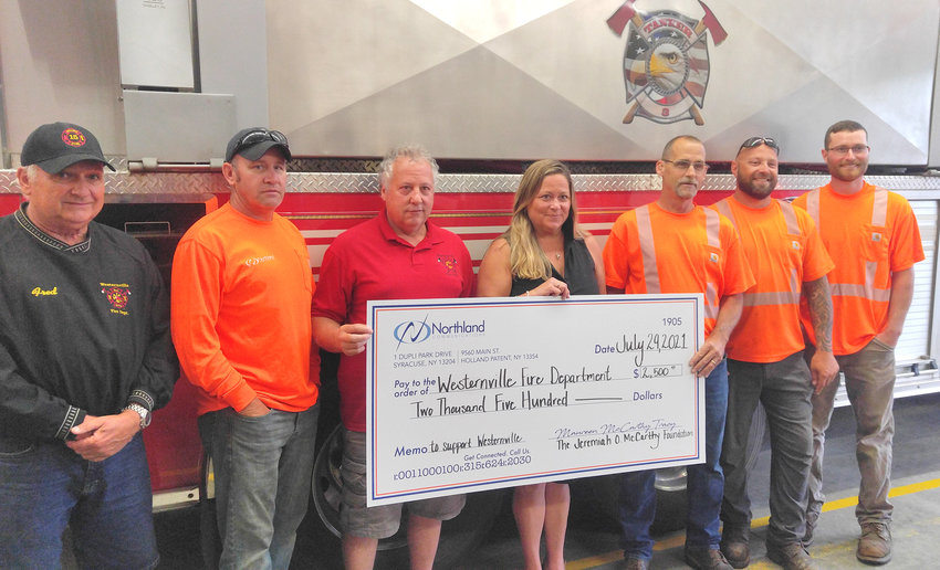 NORTHLAND DONATION — Northland Communications, of Holland Patent, donated $2,500 to both the Western Volunteer Fire Department and the Westernville Library. From left: Firefighter Fred Sherman, lineman Kevin Pratt, Western Fire Chief Michael Anania, Northland VP Maureen McCarthy Tracy, lineman Tom Warcup, lineman Anthony Gentile, and lineman Ray Edwards.